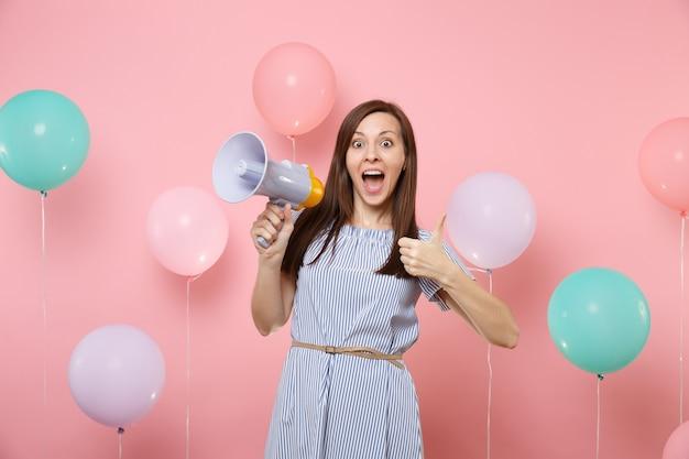 Портрет возбужденной молодой attaractive женщины, носящей голубое платье, держащего мегафон, показывая большой палец вверх на розовом фоне с красочными воздушными шарами. праздник дня рождения, концепция искренних эмоций людей.