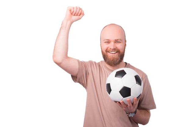 Портрет возбужденного молодого бородатого мужчины празднует успех и держит футбольный мяч