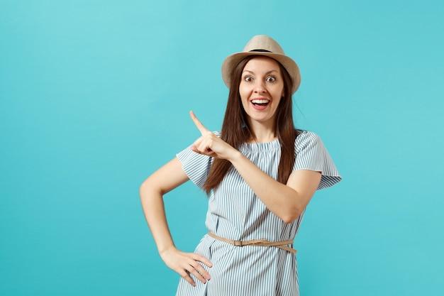 ドレス、青い背景で隔離のコピースペースに人差し指を指すわらの夏の帽子を身に着けている興奮した若いエレガントな女性の肖像画。人々の誠実な感情、ライフスタイルのコンセプト。広告エリア。