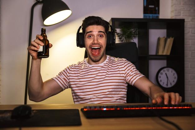 Портрет возбужденного молодого парня в наушниках, пьющего пиво, сидя за столом с компьютером в комнате и смотрящего в камеру
