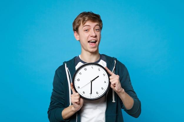 Портрет возбужденного молодого человека в повседневной одежде, держащего круглые часы, изолированные на синей стене. время уходит. люди искренние эмоции, концепция образа жизни.