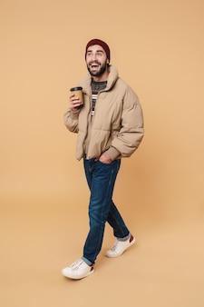Портрет возбужденного молодого человека в зимней куртке и шляпе, улыбающегося, держа чашку кофе, изолированную на бежевом