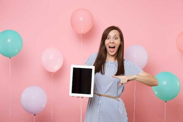 カラフルな気球とピンクの背景に空白の空の画面でタブレットpcコンピューターで人差し指を指している青いドレスで興奮した若い女性の肖像画。誕生日の休日のパーティーのコンセプト。