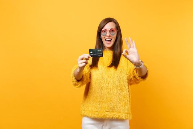 明るい黄色の背景で隔離のクレジットカードを保持し、okサインを示す毛皮のセーターのハートの眼鏡で興奮した若い女性の肖像画。人々の誠実な感情、ライフスタイルのコンセプト。広告エリア。