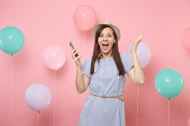 Портрет возбужденной молодой женщины в соломенной летней шляпе и синем платье с мобильным телефоном и наушниками, слушая музыку, протягивая руку на розовом фоне с красочными воздушными шарами. праздник дня рождения.