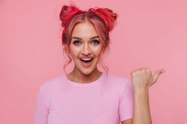 コピースペースで笑顔と人差し指を脇に向けてtシャツを着た興奮した若い女性の肖像画