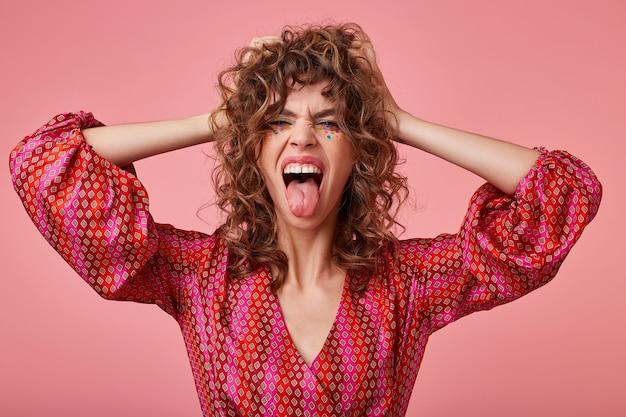 興奮した若い女性の肖像画、大声で叫び、舌を突き出し、手で耳を覆い、立っています。ピンクとオレンジの縞模様の服を着ています
