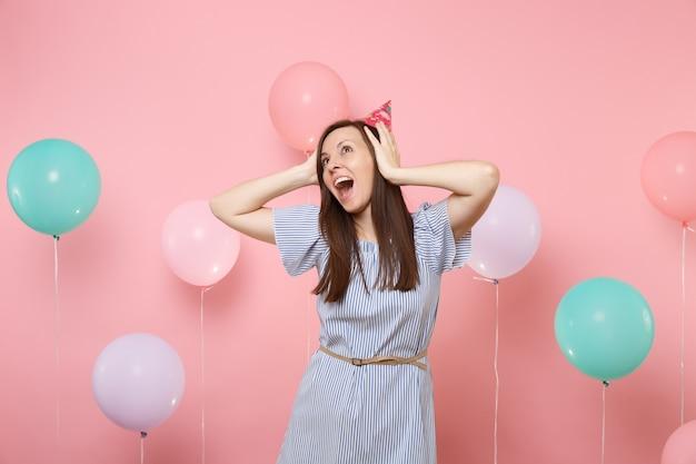 생일 모자를 쓰고 파란 드레스를 입은 행복한 여성의 초상화는 파스텔 핑크색 배경에 화려한 공기 풍선이 달린 머리에 달라붙어 있습니다. 생일 휴가 파티, 사람들은 진심 어린 감정.