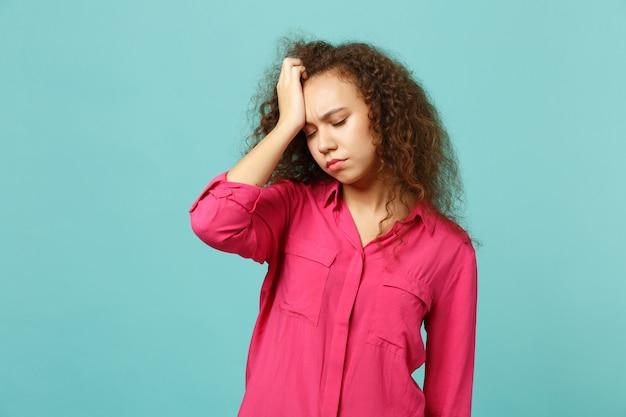 青いターコイズブルーの壁の背景に分離された頭に手を置いて目を閉じたままカジュアルな服を着て疲れ果てたアフリカの女の子の肖像画。人々の誠実な感情のライフスタイルの概念。コピースペースをモックアップします。