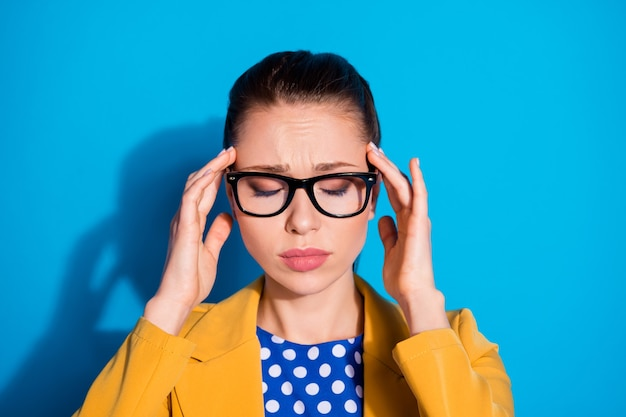 지친 과로한 소녀 마케터 칼라의 초상화는 머리 통증 covid-19 감염 증상 터치 손가락 이마를 입고 파란색 배경 위에 격리된 노란색 블레이저 재킷을 입습니다.