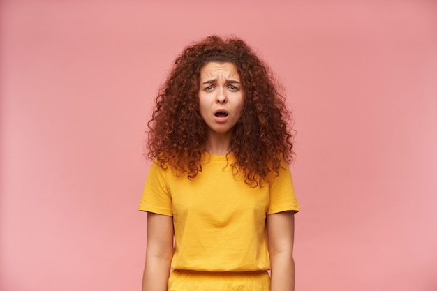 黄色のtシャツを着て巻き毛の疲れた赤毛の少女の肖像画