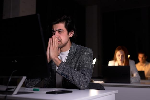 Портрет измученного серьезного кавказского мужчины, обеспокоенного работой на компьютере в офисе в ночное время, пропустил крайний срок, имеет много проблем, в темной комнате, сидит и думает. работа, бизнес-концепция