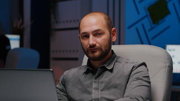 비즈니스 회사 사무실에서 책상 테이블에 앉아있는 동안 랩톱 컴퓨터를 사용하여 금융 전략을 입력 지친 일 중독 남자 관리자의 초상화