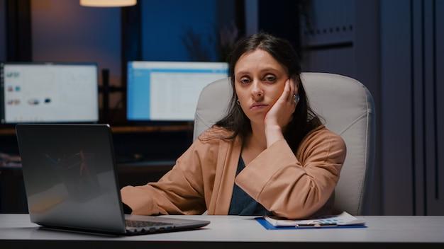 事業会社のオフィスの机のテーブルに座ってラップトップコンピューターを使用して経済統計をチェックする疲れ果てたworkaholicマネージャーの肖像画。財務戦略を入力する疲れた実業家