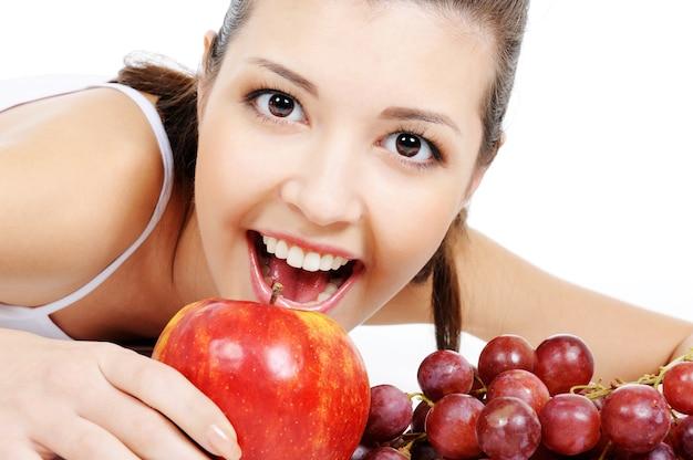 Портрет выразительной привлекательной молодой женщины с яблоком и виноградом