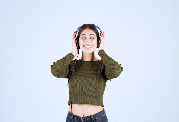 白い背景で音楽を聴いている表現力豊かな少女の肖像画。