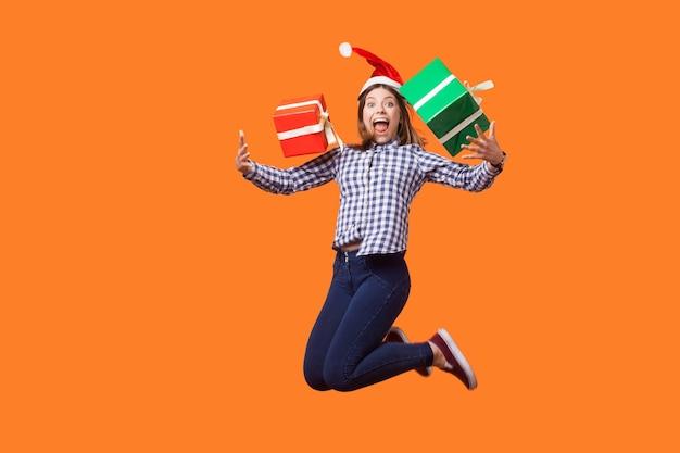 산타 모자와 체크무늬 셔츠를 입은 매우 행복한 브루네트 여성의 초상화는 기쁨을 위해 뛰고, 포장된 크리스마스 선물 상자를 들고 날아다니며 판매를 축하합니다. 오렌지 배경에 고립 된 실내 스튜디오 촬영