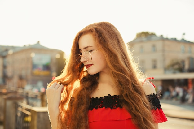 안경을 쓴 주근깨가 있는 멋진 빨간 머리 모델의 초상화, 저녁 부드러운 햇빛 아래 포즈. 텍스트를 위한 공간