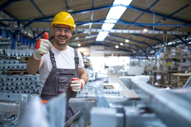 Портрет фабричного рабочего в защитном снаряжении, подняв палец вверх в производственном цехе