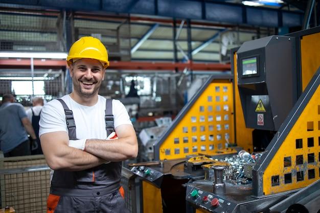 Портрет фабричного рабочего со скрещенными руками возле промышленной машины на производственном предприятии