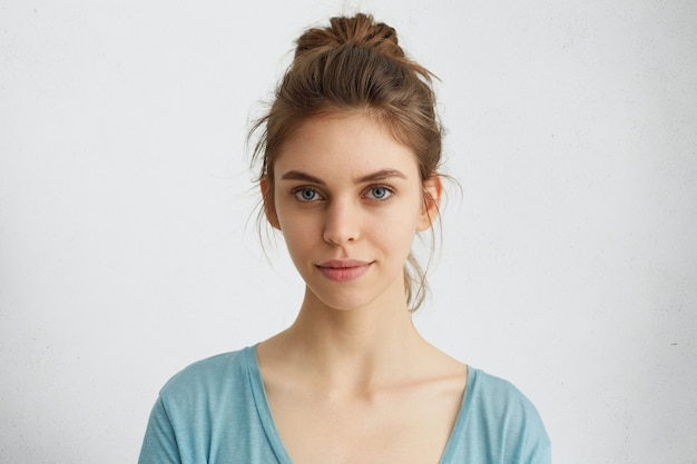 暖かい青い目、唇の乾燥、直接見ている健康な皮膚を持つ金髪の女性の肖像画。さりげなくポーズをとって美しい姿の魅惑的な女の子