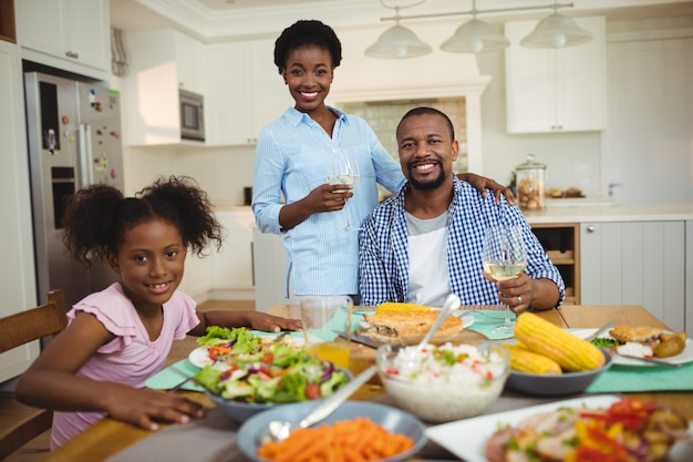 自宅のダイニングテーブルで食事をしている家族の肖像