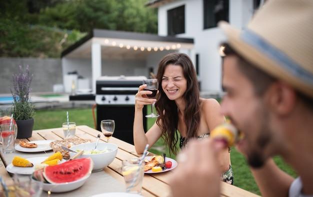 庭のバーベキューで屋外のテーブルに座って、ワインを食べたり飲んだりする家族の肖像画。