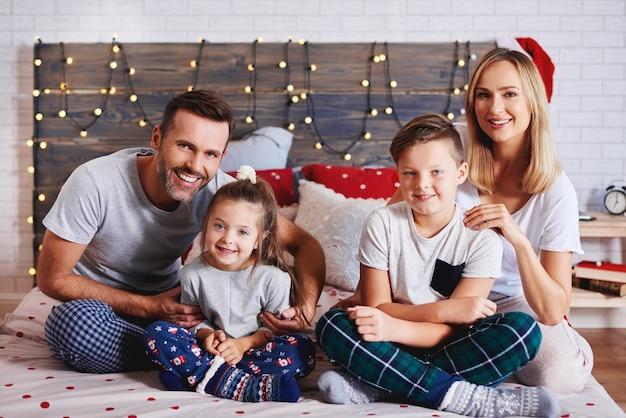 침대에서 크리스마스 아침을 보내는 가족의 초상화