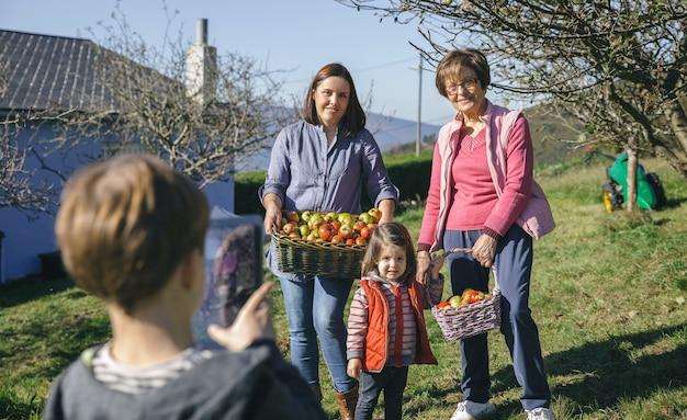 귀여운 소년이 전자 태블릿으로 사진을 찍는 동안 포즈를 취하는 고리버들 바구니에 신선한 유기농 사과를 든 가족의 초상화. 세 가지 다른 세대 개념입니다.