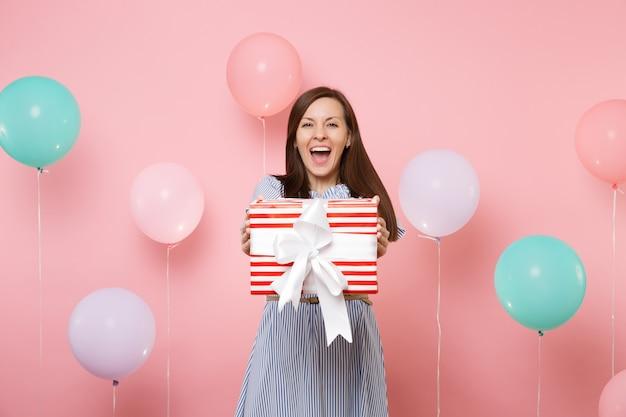 화려한 공기 풍선과 함께 파스텔 핑크색 배경에 선물이 있는 빨간색 상자를 들고 파란 드레스를 입은 매혹적인 행복한 젊은 여성의 초상화. 생일 휴가 파티, 사람들은 진심 어린 감정 개념입니다.