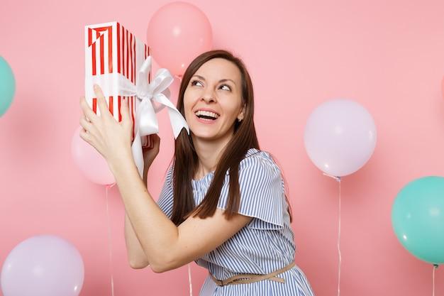 화려한 공기 풍선과 함께 파스텔 핑크색 배경에 선물이 있는 빨간 상자를 들고 파란 드레스를 입은 매혹적인 웃는 젊은 여성의 초상화. 생일 휴일 파티, 사람들이 진실한 감정 개념