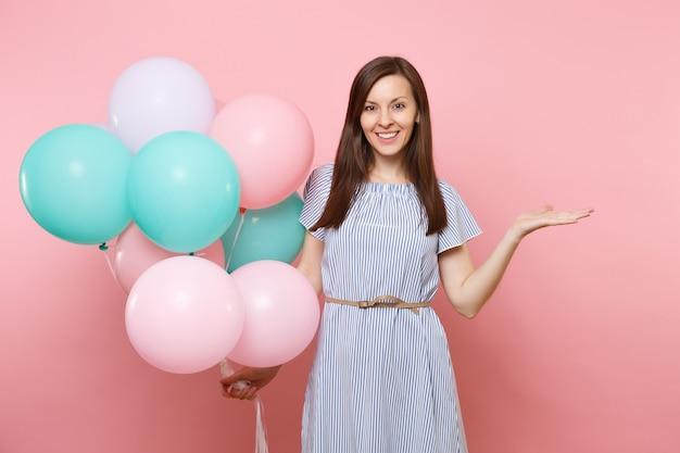 明るいトレンドのピンクの背景で隔離のコピースペースに手を脇に向けてカラフルな気球を保持している青いドレスの魅力的な若い幸せな女性の肖像画。誕生日の休日のパーティーのコンセプト。