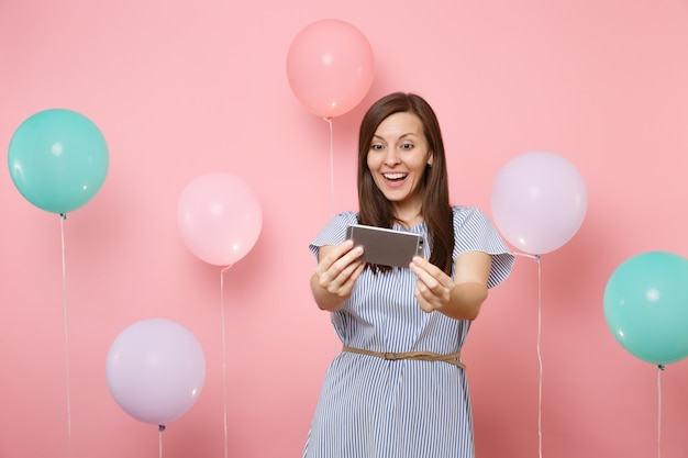 파란 드레스를 입고 파스텔 핑크색 배경에 화려한 공기 풍선으로 셀카를 찍고 있는 매력적인 젊은 행복한 여성의 초상화. 생일 휴가 파티, 사람들은 진심 어린 감정 개념입니다.