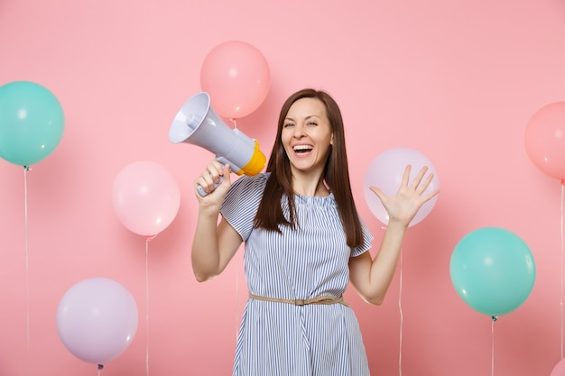 Портрет очаровательной молодой счастливой женщины, носящей голубое платье, держащей мегафон, разводящей руки на ярком трендовом розовом фоне с красочными воздушными шарами. праздник дня рождения, люди искренние эмоции