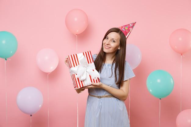 화려한 공기 풍선이 있는 파스텔 핑크색 배경에 선물이 있는 빨간색 상자를 들고 생일 모자 파란색 드레스를 입은 매혹적인 젊은 여성의 초상화. 생일 휴가 파티, 사람들은 진심 어린 감정.