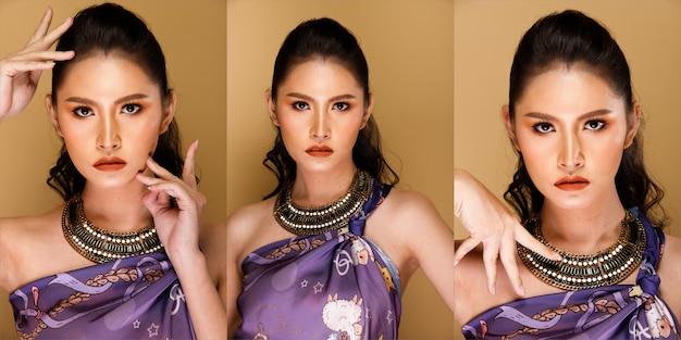 패션 20대 아시아 여성의 초상화는 브러시와 컬러 립스틱에 아름다운 업데이트 메이크업 아티스트를 가지고 있으며, 그는 세련된 아이템을 착용하고, 검은 머리는 노란색 배경 격리된 복사 공간 위에 카메라를 봅니다.