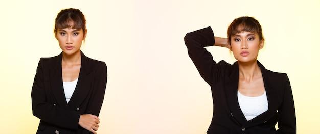 ファッション20代の肖像アジアの女性日焼けした肌は美しい黒髪スタイルのファッション化粧品を構成しています。女の子は黒のスーツを着てパステルカラーの笑顔をポーズ背景分離コピースペーステキストロゴ