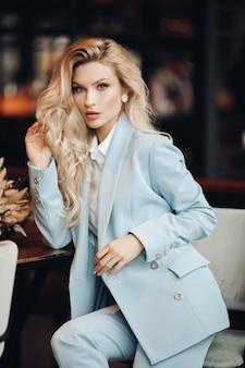 Портрет женщины блондинки моды моды представляя сидя на стуле смотря средний выстрел камеры. очаровательная роскошная стильная девушка в модном костюме, расслабляющаяся в общественном кафе или ресторане