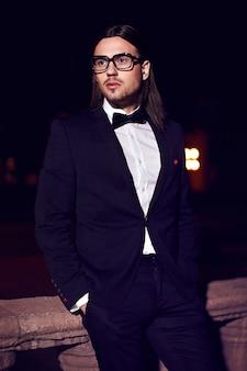 ファッションエレガントな長い髪の若い男の肖像画。夜の通りに口ひげと黒のスーツで魅力的でハンサムな男性モデル