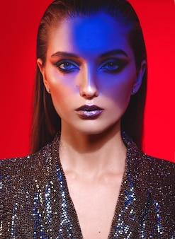 スタジオでネオンの光の中で赤い背景に黒の輝くドレスで長い髪とスタイリッシュなメイクのファッションの女の子の肖像画