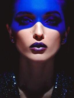 スタイリッシュなメイクとスタジオの黒い背景に彼女の顔に青いネオンライトとファッションの女の子の肖像画