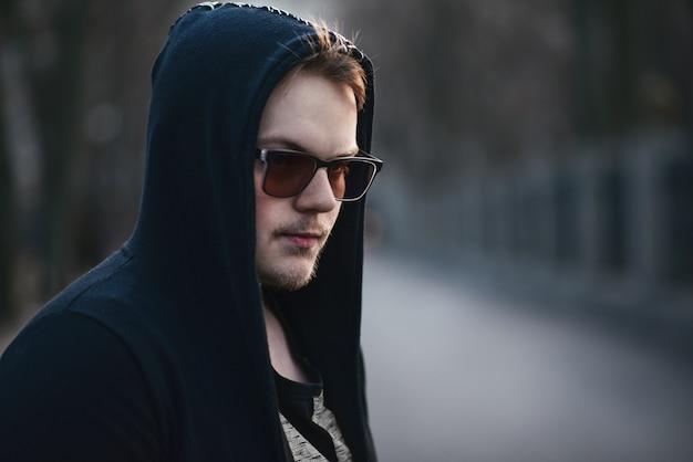 Портрет модного человека в черном свитере с капюшоном и солнцезащитными очками