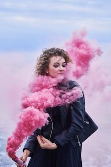ピンクの発煙弾でポーズをとって黒い服を着たファッションモデルの女の子の肖像画