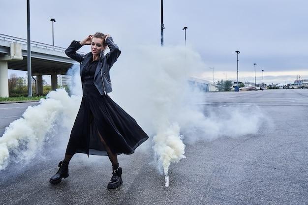 煙、白い霧の影響で黒い服を着たファッションモデルの女の子の肖像画