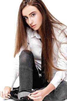 白いシャツと白い背景で隔離のネクタイの長い髪のファッションモデルの肖像画