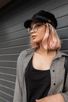 街の灰色の壁の近くに立っている帽子とメガネのファッショナブルなカジュアルシャツのピンクの髪を持つファッションきれいな女性モデルの肖像画