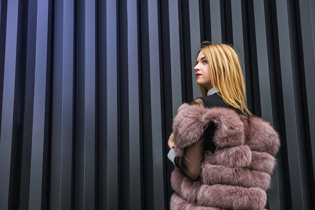 ファッションの女性の肖像画。暗い壁の背景にポーズをとって毛皮のコートの美しい女性