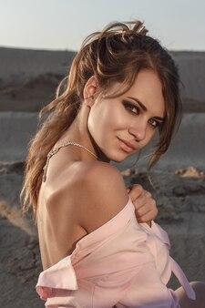 ピンクの長いシャツの屋外でファッション女性の肖像画