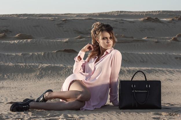 黒のバッグ屋外でピンクのロングシャツのファッション女性の肖像画