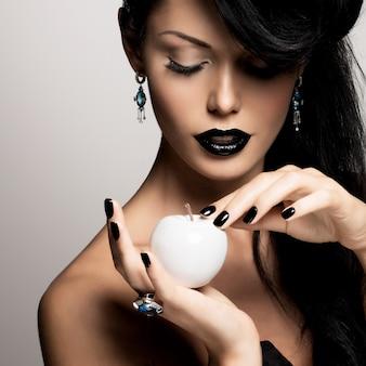 モダンな髪型と白いリンゴと黒い色の唇を持つファッション女性の肖像画